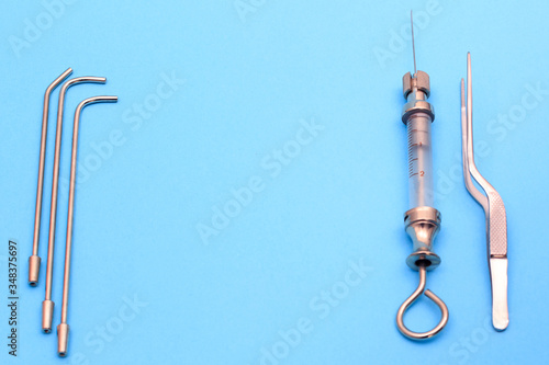 vintage syringe for intrauterine infusions and tonsillectomy on a blue background Canvas Print