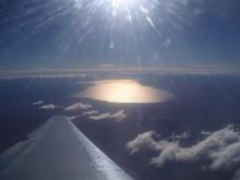 Sun Shining Over Lake Seen Through Airplane Window