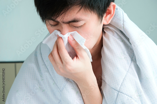 Fotografie, Obraz Sick man is flu, using a paper napkin and he have a runny nose