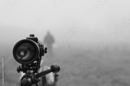 Obraz na płótnie Close-up Of Sniper Aiming At Man On Field During Foggy Weather