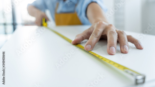 Leinwand Poster Men's hands hold a measuring tape measuring with flexible ruler for home renovation