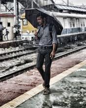 Young Man Carrying Umbrella While Walking On Railroad Platform During Rainy Season