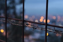Close-up Of Barbed Wire Against Defocused Lights
