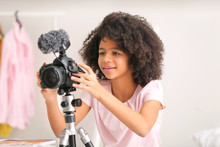 African-American Teenage Blogger Adjusting Camera For Recording Video At Home