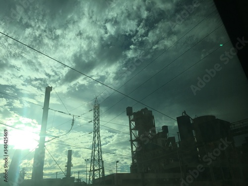Obraz na plátně Low Angle View Of Buildings And Electricity Pylon Against Cloudy Sky