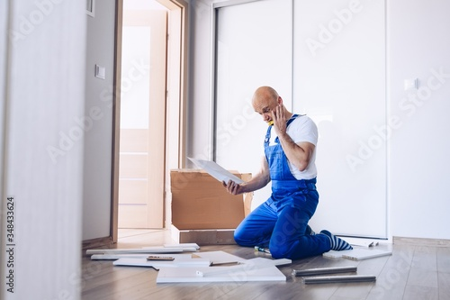 Photo Nervous man assembling cabinet and reading manual