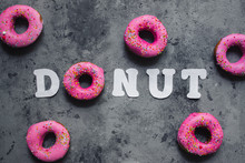 Text Word Donut Made Of One Pink Rainbow Sprinkles Doughnut And White Paper Letters On Grey Dark Concrete Background. Free Copy Space. Top View