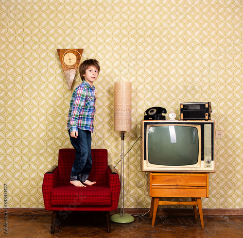 Photo Vintage art portrait of liitle boy jumping on armchair in room with interior from 70s 20th century, retro stylization, image toned