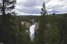 Big Waterfall In The Forest Between Green Trees With Cloudy Sky Above In Yellowstone National Park World Famous Landmark In The World And Rocky View As Travel Concept For Wallpaper From USA