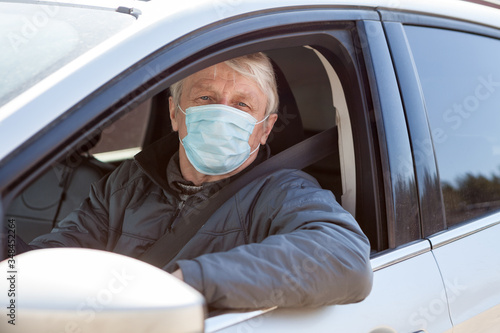 Foto Senior man a driver using surgical mask to prevent virus infection, taxi driver