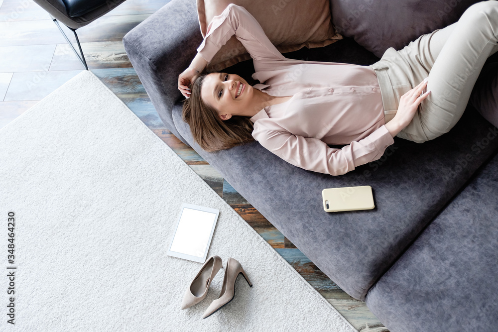 Fototapeta Top view happy healthy young smiling woman enjoying weekend and forced quarantine while lying on cozy sofa at home. Concept of pleasure social media communication and online shopping