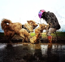 Playful Girl With Australian Shepherd On Muddy Field Against Sky