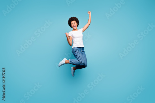 Obraz Full length photo of ecstatic dark skin wavy lady jumping high sporty competitive person celebrating goal match fan wear casual white t-shirt jeans isolated blue color background - fototapety do salonu