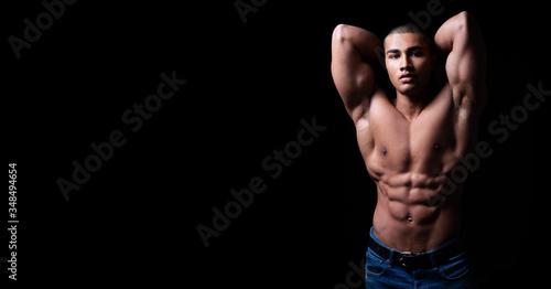 Portrait eines attraktiven, muskulösen und hübschen Mannes oberkörperfrei vor schwarzem Hintergrund