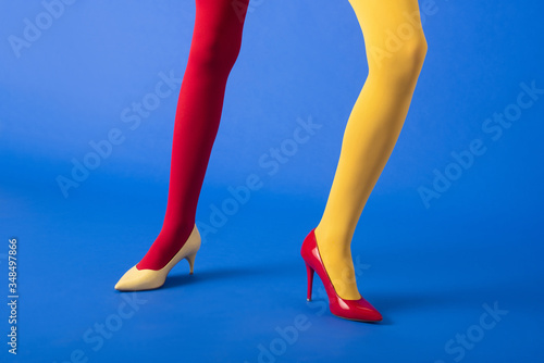 Valokuva cropped view of woman in yellow and red tights and heels posing on blue