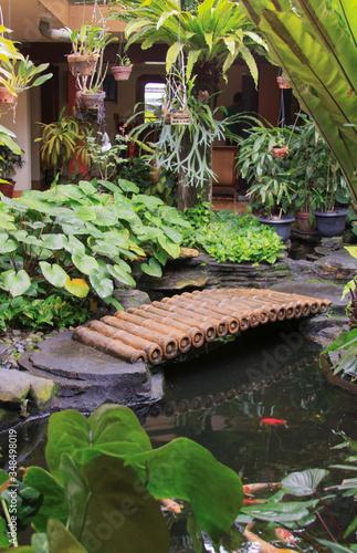 фотография Bamboo bridge over pond in patio garden design