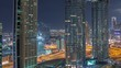 Dubai downtown skyscrapers amazing aerial view at night timelapse with highway and crossroad, Dubai, United Arab Emirates. Illuminated modern towers and construction site