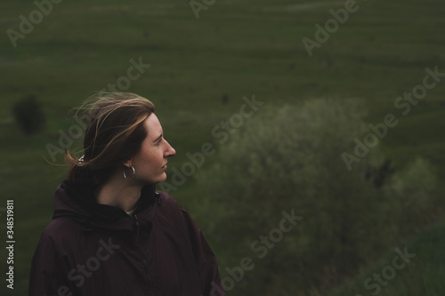 Photo Woman in a rain anorak stands on the hill, deep green background