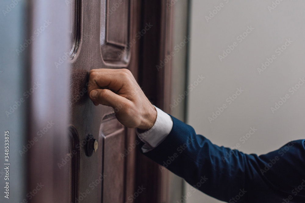 Fototapeta Cropped view of collector knocking on door with hand