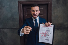 Angry Collector With Documents With Foreclosure Lettering Pointing With Finger And Shouting In Room