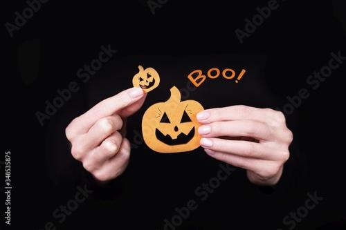 Vászonkép Female hands holding funny little pumpkins on black background