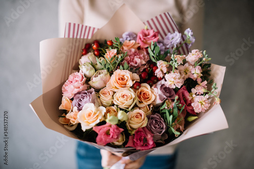 Very nice young woman holding big beautiful blossoming bouquet of fresh hydrangea, roses, eustoma flowers in burgundy and pink colors on the grey wall background © anastasianess