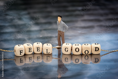 Miniature model of man and wooden cubes with feel good inscription strung on a thread on reflective table.