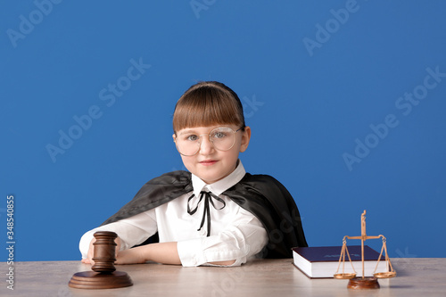 Portrait of little judge sitting at table against color background Fototapet