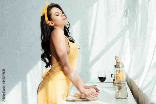 Side view of naked girl in apron rolling dough on kitchen worktop Slika na platnu