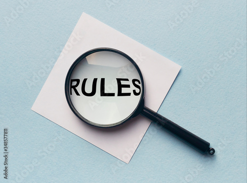 Valokuva Magnifying glass or loupe with the word rules on a white memo note on blue background