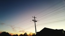 Low Angle View Of Electricity Pylon By House Against Sky