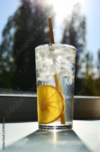 glass glass with water lemon ice and yellow tube against the background of the window with a bright sun view from below