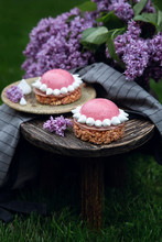 Raspberry Tartlets On The Little Wooden Table And A Violet Lilac In The Background