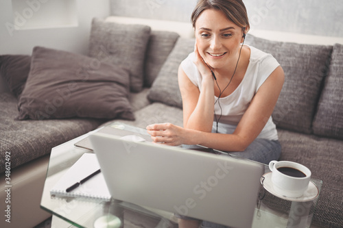 Attractive happy young student studying online at home, using laptop computer, headphones, having video chat, waving Fotobehang