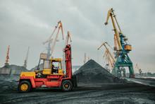 Heavy Duty Forklift Truck Parked Near Huge Pile Of Coal. Dock Distribution Center