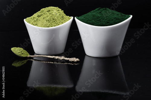 Fényképezés An isolated tablespoon of dried organic wheat grass and spirulina powder, on whi
