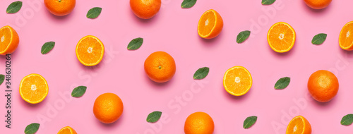 Obraz Fruit pattern, creative summer concept. Fresh juicy whole and sliced orange, mint leaves on pink background. Flat lay Top view. Minimalistic background with citrus fruits, vitamin C. Pop art design - fototapety do salonu