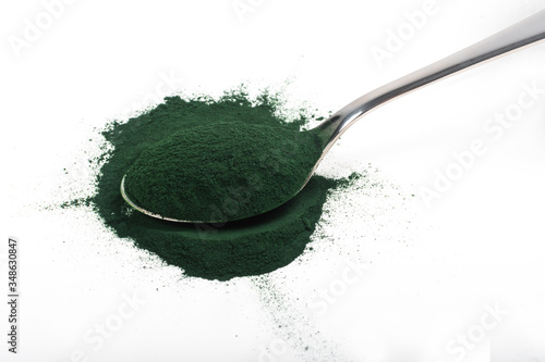 Vászonkép An isolated tablespoon of dried organic spirulina algae powder, on white or rustic background