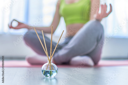 Photo Fitness woman in lotus pose with aroma sticks and essential oil bottle during yoga training, aromatherapy treatments and meditation