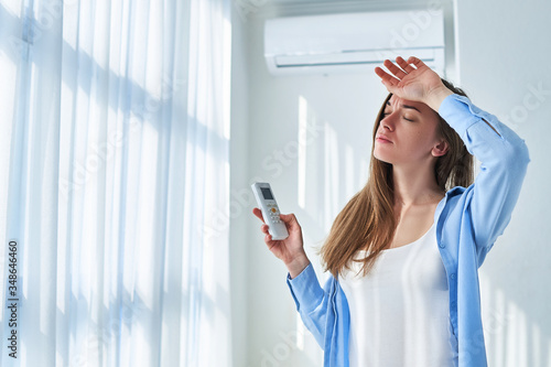 Sweating woman suffering from heat and hot weather cools down with air conditioning at home Canvas Print