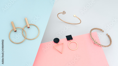 Fototapeta Modern golden jewelry bracelets and earrings on blue and pink paper background