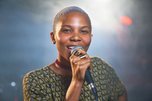 Portrait Happy Young Female Musician Singing Into Microphone