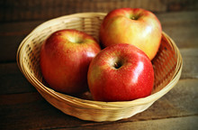 Three Red Apples On Wicker Basket