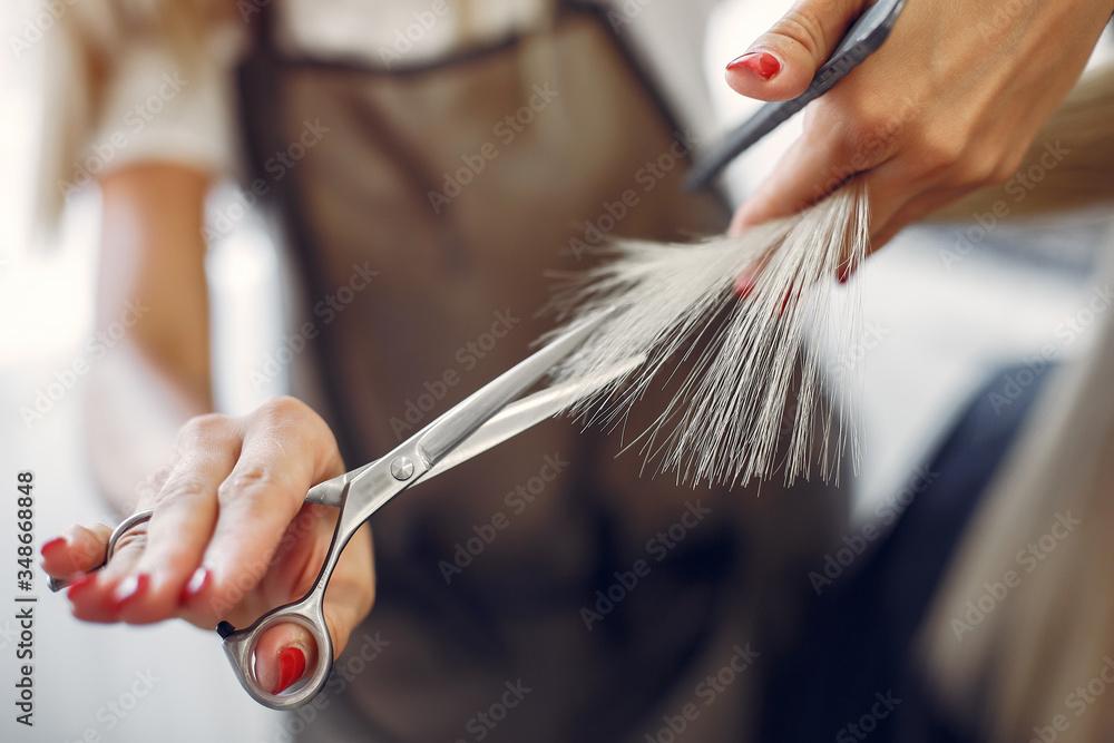 Fototapeta Hairdresser cut hair her client. Woman in a hair salon