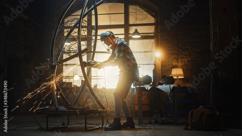 Fototapeta Talented Innovative Tomboy Female Artist Uses an Angle Grinder to Make an Abstract, Brutal and Expressive Metal Sculpture in a Workshop. Contemporary Fabricator Creating Modern Steel Art. obraz