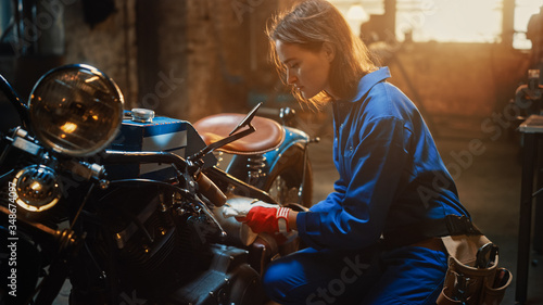 Young Beautiful Female Mechanic is Working on a Custom Bobber Motorcycle Fototapet