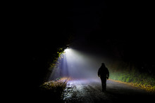 Rear View Of Silhouette Man Walking On Road At Night