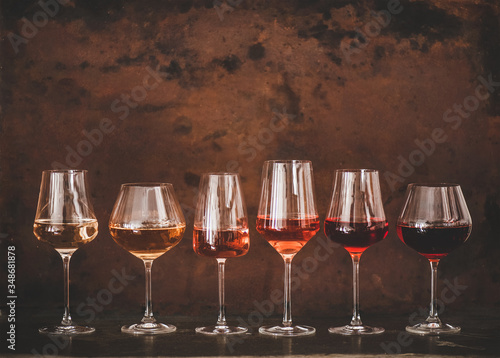 Fototapeta Various shades of Rose wine in stemmed glasses placed in line from light to dark colour on concrete table, rusty brown background behind, copy space. Wine bar, wine shop, wine tasting concept obraz