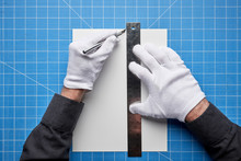 A Person Wearing White Cotton Gloves Cutting Paper With A Sharp Blade.
