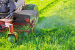 canvas print picture - Close up of man using a lawn mower a gardener cutting grass by lawn mower